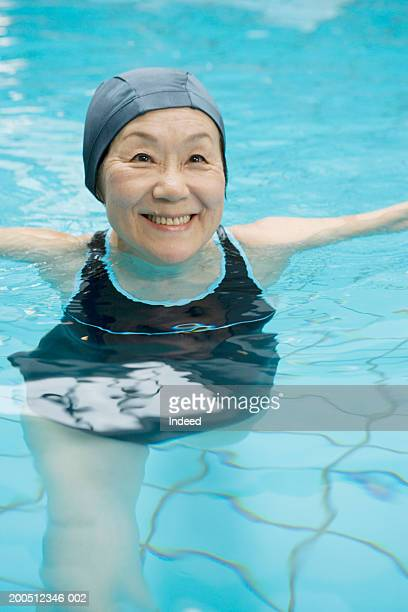 Senior women exercising in swimming pool, smiling, elevated view