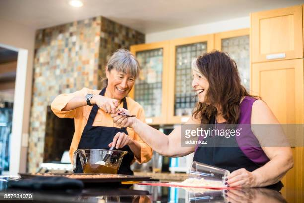 senior women friends cooking in kitchen - delegating stock photos and pictures