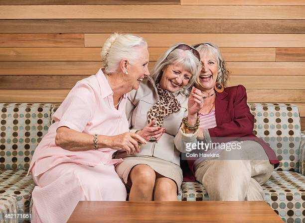 Senior women friends laughing on sofa