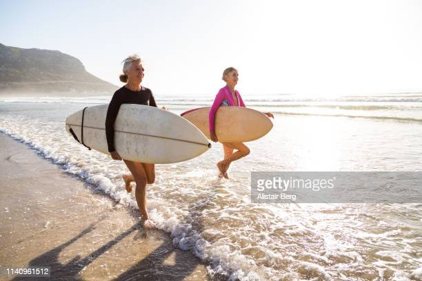 Senior women going for a morning surf in the sea