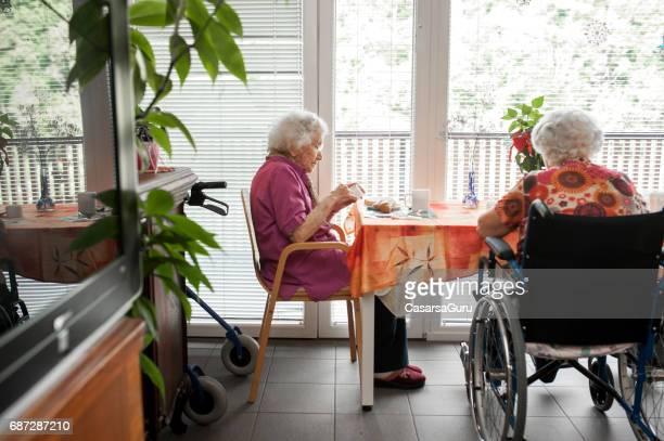 Senior Women Having Breakfast Near The Window In The Retirement Community