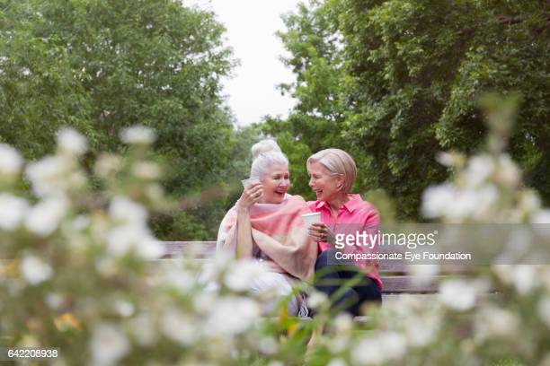 Senior women having coffee together in park