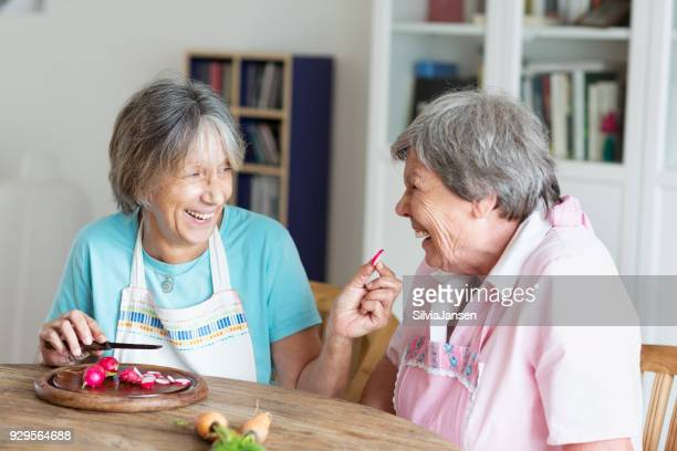 senior women having fun cooking together
