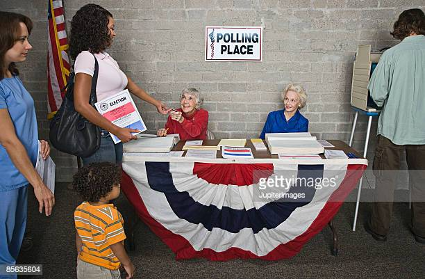 senior women helping voters at polling place - participant stock pictures, royalty-free photos & images