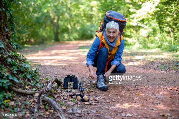 senior women hiking in spring forest. - woodland stock pictures, royalty-free photos & images