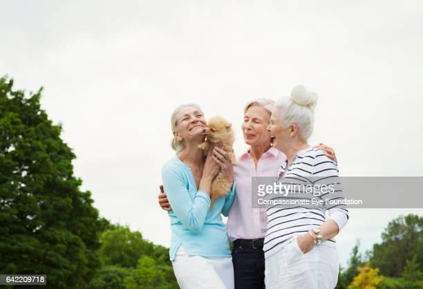 Senior women holding dog in park