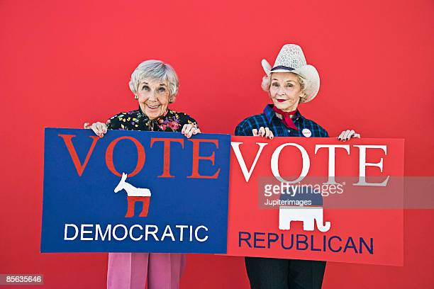 Senior women holding political party signs