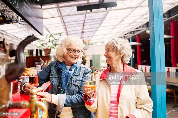 Senior women holding wineglass and smiling while looking at each other in restaurant