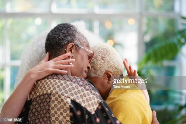 senior women hugging - grief stock pictures, royalty-free photos & images