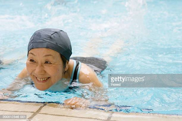 Senior women in swimming pool, holding edge, smiling