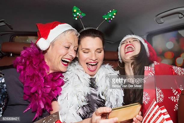 Senior women laughing at photo on phone in car.
