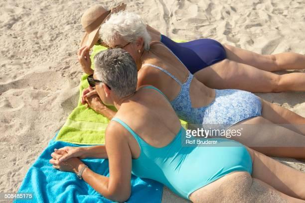 senior women laying on beach - roupa de natação - fotografias e filmes do acervo