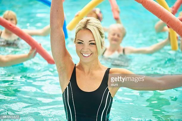 senior women led by female instructor at water aerobics