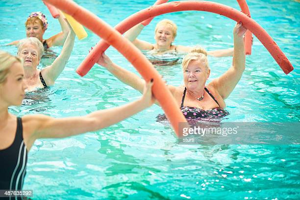 senior women led by female instructor at water aerobics