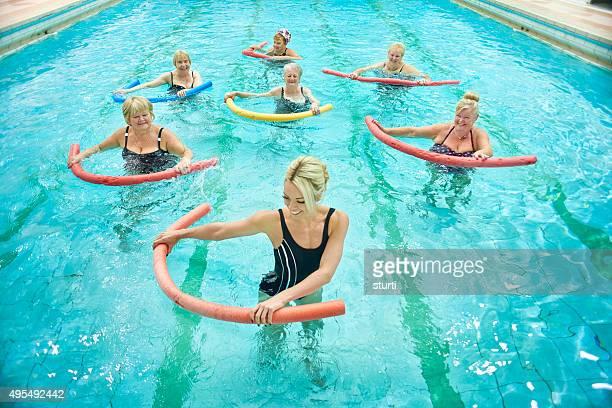 senior women (年配の女性のインストラクターによる水中エアロビクス - 室内プール ストックフォトと画像