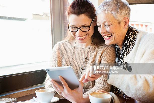 Senior women looking at digital tablet in cafe.