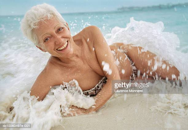 senior women lying in water on beach, smiling, portrait - old woman in swimsuit stock pictures, royalty-free photos & images