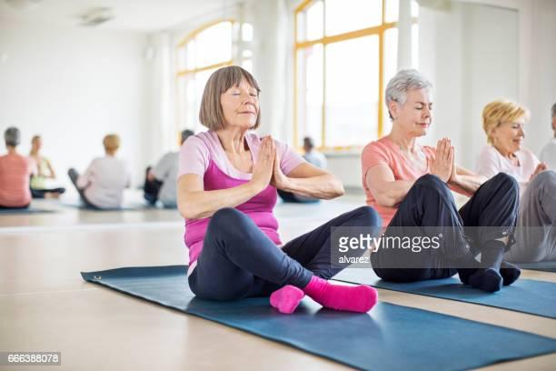 Senior women meditating in yoga class