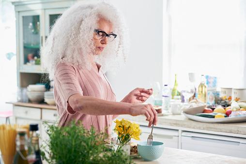 senior women mixing bowl in kitchen - gettyimageskorea