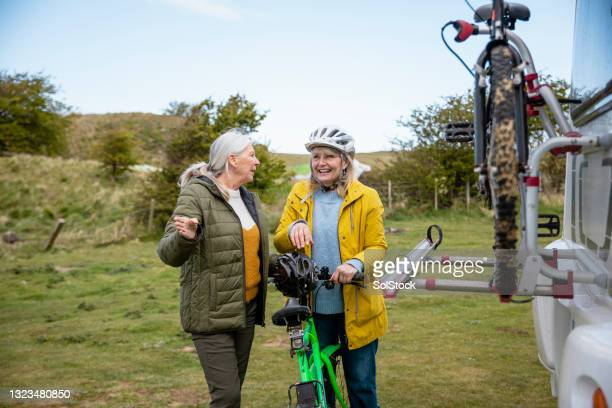 senior women on a bike ride - headwear stock pictures, royalty-free photos & images
