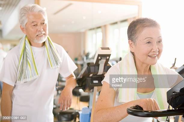 Senior women on exercise bike in gym, senior man looking on, smiling