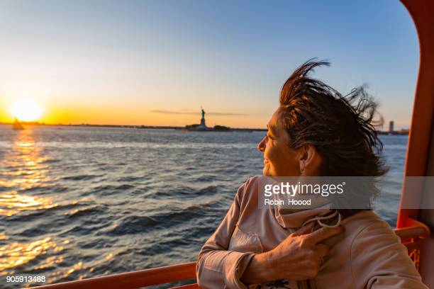 senior women on sunset near the statue of liberty - new york city - ferry stock pictures, royalty-free photos & images