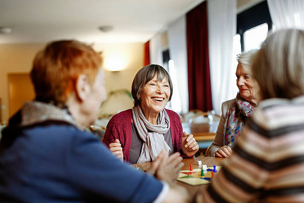 senior women playing board game - care home stock pictures, royalty-free photos & images