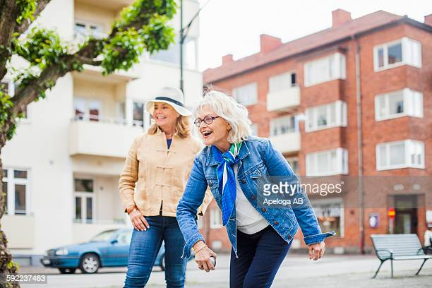 Senior women playing boule on field by street against buildings