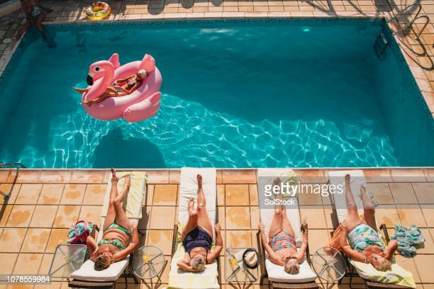 senior women relaxing by the poolside - women sunbathing stock photos and pictures