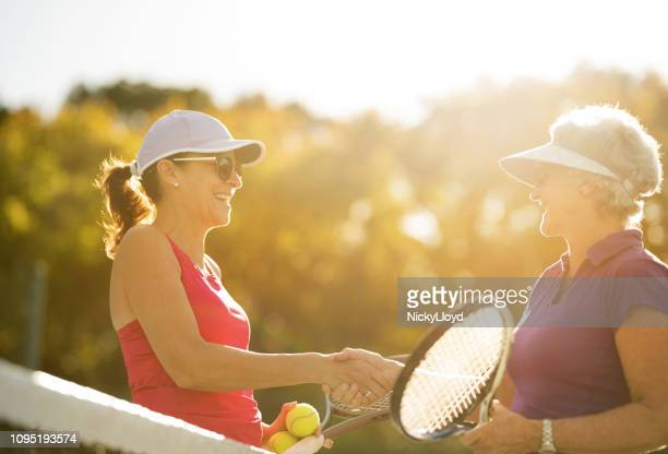senior women shaking hands after a friendly game of tennis on bright sunny day. - tennis stock pictures, royalty-free photos & images
