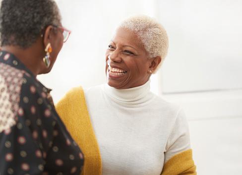 senior women smiling and talking to friend - gettyimageskorea