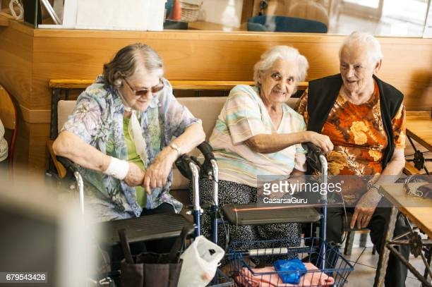 senior women socializing  in the lobby of the retirement community - residential care stock photos and pictures