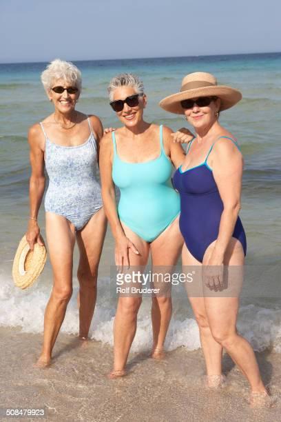 senior women standing in waves on beach - badebekleidung stock-fotos und bilder