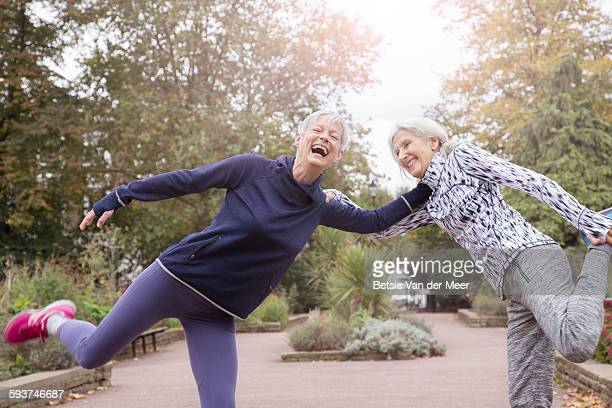 senior women stretching legs in park. - female friendship stock pictures, royalty-free photos & images