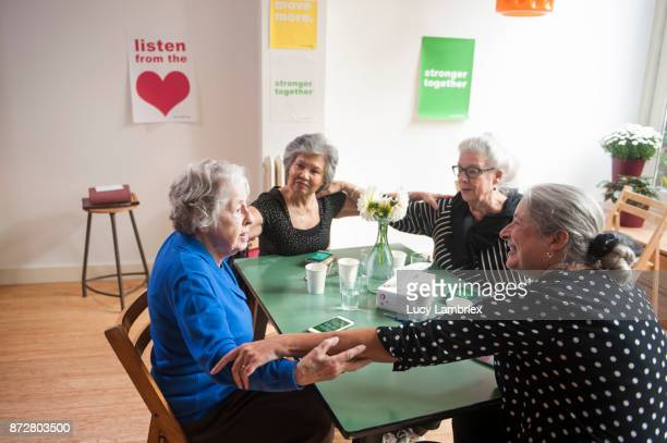 Senior women support group gathering and holding one another