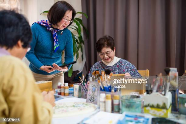 Senior women taking a painting class at a nursing home