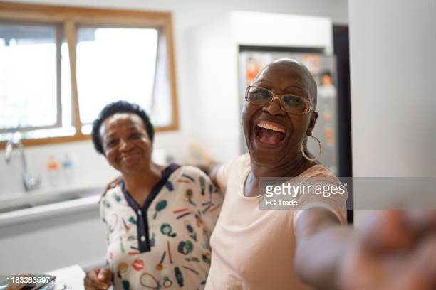 senior women taking a selfie in the kitchen - baby boomer stock pictures, royalty-free photos & images