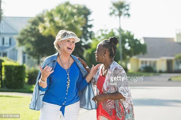 Femmes âgées prenant une promenade sur une journée ensoleillée, discuter