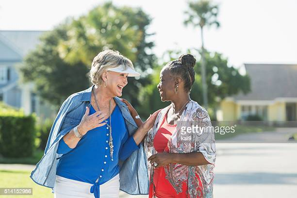 senior women taking a walk on a sunny day, talking - female friendship stock pictures, royalty-free photos & images