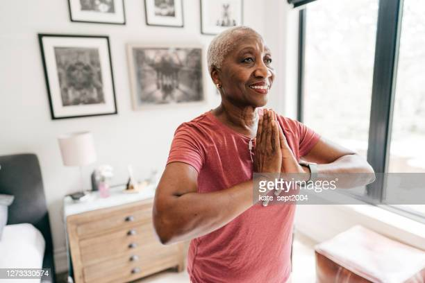 senior women taking care of her wellbeing, she is exercising at home in sportswear - active lifestyle stock pictures, royalty-free photos & images