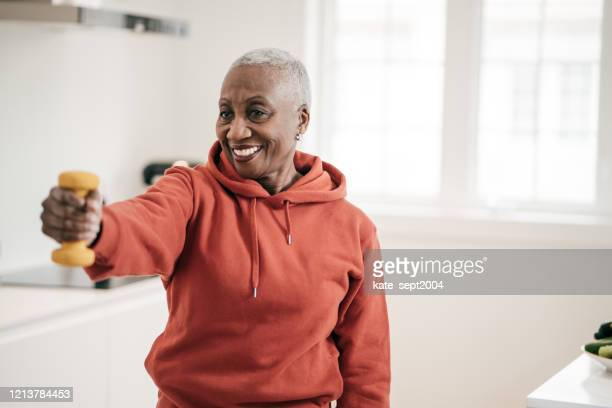 senior women taking care of herself  she exercise with  dumbbells at home - physical therapy stock pictures, royalty-free photos & images