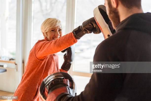 seniorinnen trainieren mit instruktor in boxgymnastik - kampfsport stock-fotos und bilder