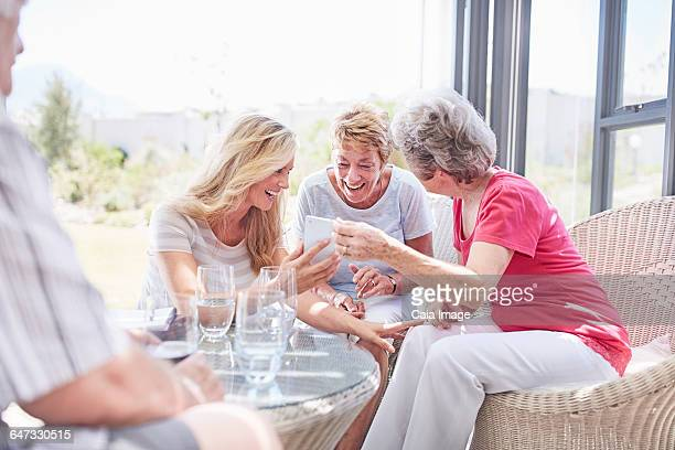 Senior women using cell phone on patio