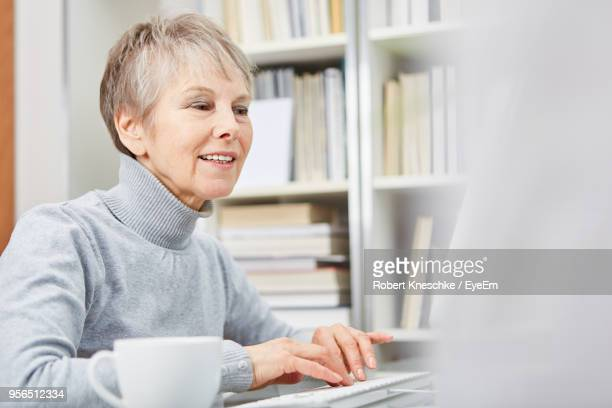 senior women using laptop at home - mock turtleneck stock pictures, royalty-free photos & images