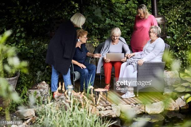 senior women using laptop on garden terrace - water garden stock pictures, royalty-free photos & images