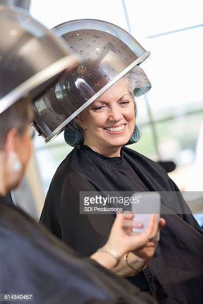 Senior women using smart phone during hairstyling appointment in salon