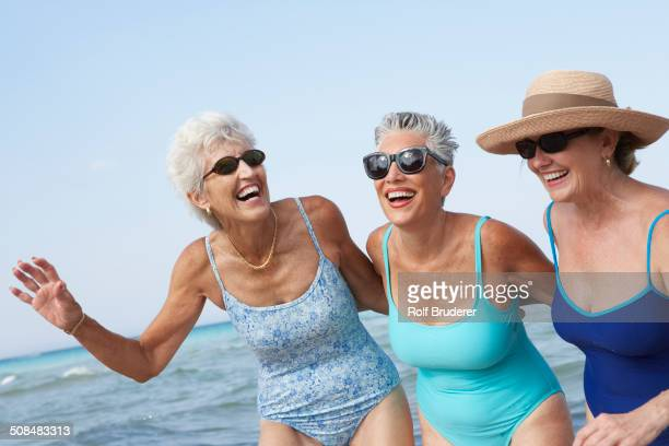 senior women walking on beach - old woman in swimsuit stock pictures, royalty-free photos & images