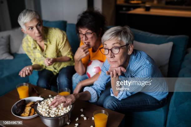 senior women watching football on tv - match sport stock pictures, royalty-free photos & images