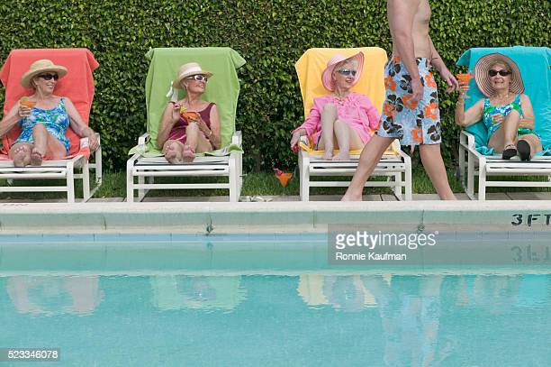 senior women watching young man walk by - women sunbathing stock photos and pictures