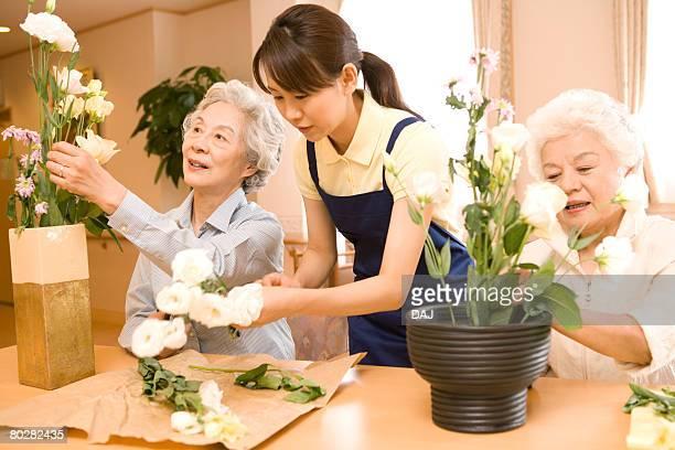 Senior women with female nurse performing Japanese flower arrangement